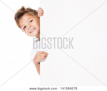 Portrait of smiling young boy with bruise, peeking through billboard, isolated on white background. Close up of happy cute kid with blank white poster. Child holding empty placard and looking at camera.