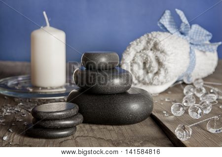 Blue white spa set. Massage stones candle towel on a wooden table.