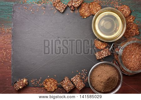 flax seeds and products thereof: linseed oil flax flour energy bars and crackers from flax seeds on a dark a stony background (top view)