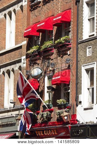 LONDON, UNITED KINGDOM - SEPTEMBER 12 2015: The Globe pub and kitchen in London with its red curtains on the facade