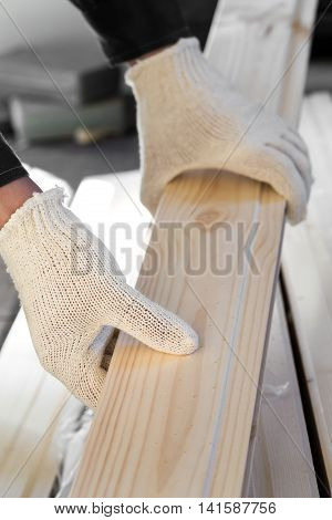 Hands In Fabric Gloves Holding Wooden Plank