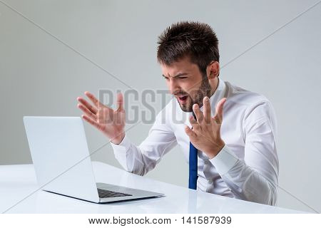 the young man is nervous. It uses a computer while sitting at a table. Office clothing