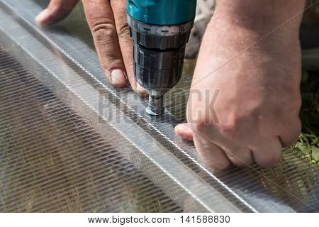 Worker Screwing Screw Into Polycarbonate