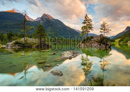 Beautiful scene of trees on a rock island in idyllic scenery at charming mountains at sunrise time in summer, Lake Hintersee National park Berchtesgadener Land, Upper Bavaria, Germany, Europe