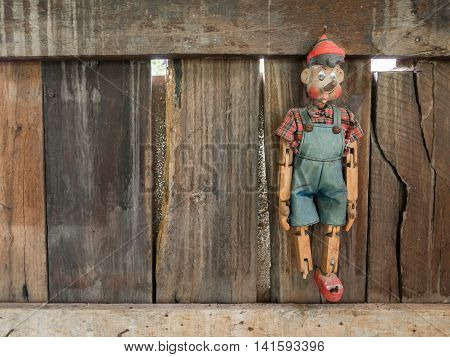 Old Pinocchio wooden marionette hang on wall