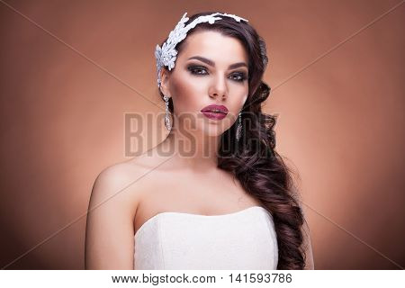 Gorgeous bride with amazing hairstyle in studio photo on brown background. Brides portrait and proffesional wedding make up