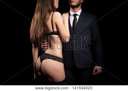 Luxury And Power Concept. Businessman In Suit Holding A Naked Woman In Bikini