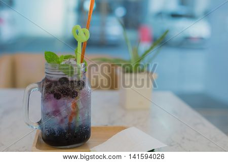cold blueberry soda with ice fresh served in glass wooden tray in cafe or restaurant or coffee shop