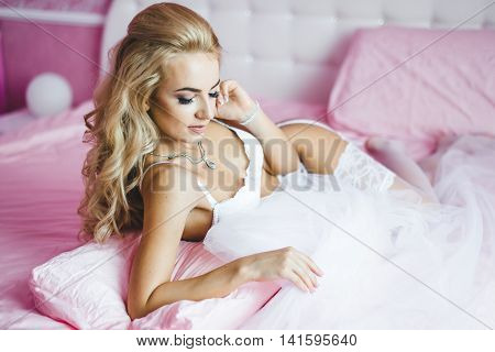Beautiful sexy young women underwear lying on a bed with a veil in hands. Last preparations for the wedding. Morning the bride.