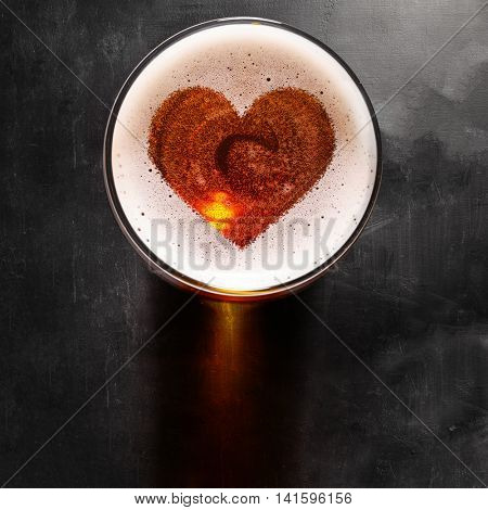 loving beer, heart symbol on foam in glass on black table, view from above