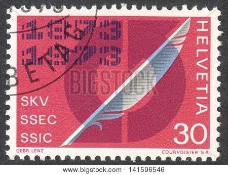 MOSCOW RUSSIA - CIRCA MAY 2016: a post stamp printed in SWITZERLAND shows a Quill Pen and arrows in circle dedicated to Swiss Association of Commercial Employees centenary circa 1973