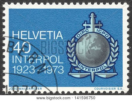 MOSCOW RUSSIA - CIRCA APRIL 2016: a post stamp printed in SWITZERLAND shows INTERPOL emblem dedicated to the 50th anniversary of INTERPOL circa 1973