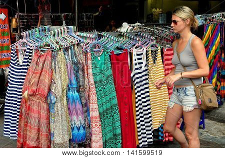 Bangkok Thailand - December 17 2012: Woman looking at women's clothing displayed in front of on touristy Khao San Road