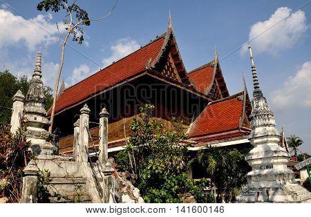 Ayutthaya Thailand - December 21 2010: White Chedis and teak wood monastic houses with high gables and chofah ornaments at c. 1503 Wat Na Phramane