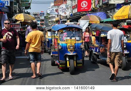 Bangkok Thailand - January 19 2013: Tuk-tuk taxis and pedestrians share bustling touristy Khao San Road