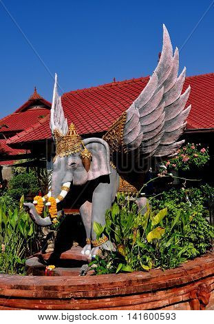 Chiang Mai Thailand - December 29 2012: Statue of a winged elephant with floral offerings left on its tusks at Wat Chomphu