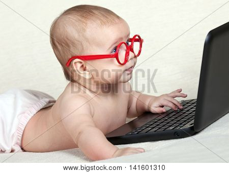 Little baby in red glasses looking at the laptop display