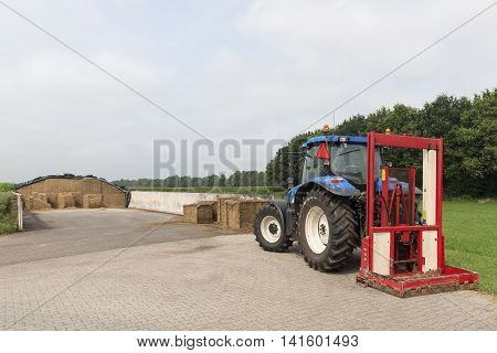 Blue tractor with a red bale slicer for cutting off silage bales