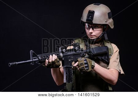Young girl in helmet gloves and ballistic glasses with gun on black background