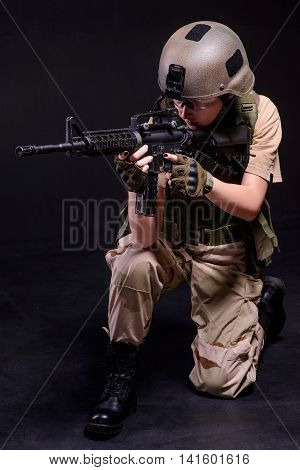 Woman soldier in helmet aiming from rifle black background