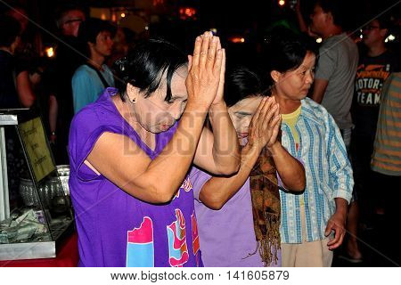 Chiang Mai Thailand - December 22 2012 : Thai women with clasped hands praying to a gilded Buddha at the Sunday Walking Street market on Thanon Ratchadamnoen
