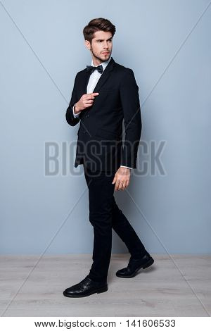 Portrait Of Handsome Young Man In Black Suit And Bow Tie