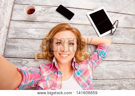 Pretty Happy Blonde Lying On Floor And Making Selfie