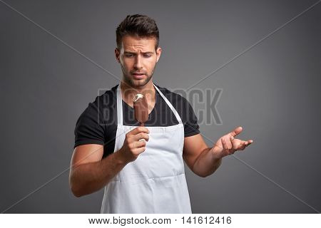 A handsome young barista man feeling confused while having an ice-cream