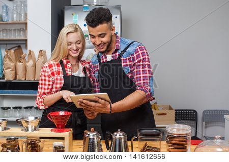 Barista coffee shop couple using tablet computer happy smile at bar counter mix race man woman small business