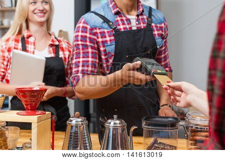 Close up credit card payment coffee shop bar counter barista serving client paying bill woman happy smile to customer