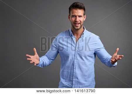 A handsome young man looking uncomprehendingly in to the camera in front of a grey background in a studio