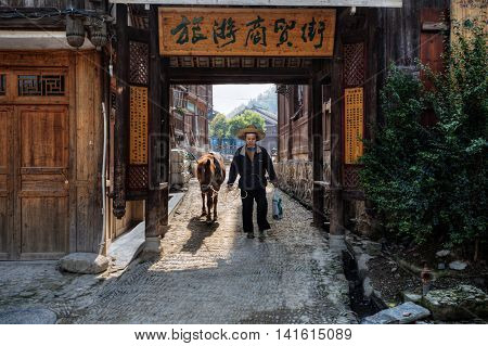 Zhaoxing Dong Village Guizhou Province China - April 9 2010: Asian man wearing a hat leads the horse by the reins passes through the old wooden entrance gate of the village Dong ethnic minority.