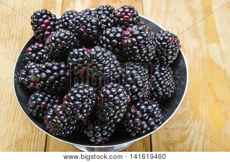 fresh blackberry on a wooden table in iron ware