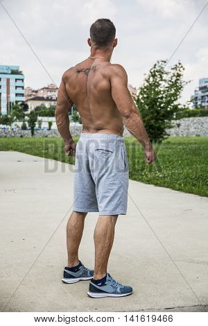 Back of Muscular Shirtless Hunk Man Outdoor in City Setting. Showing Healthy Body While Looking away