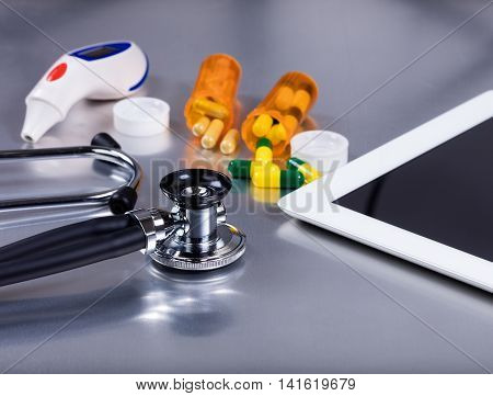 Medical stethoscope on exam table with medicine pills thermometer bottles and mobile computer. Selective focus on stethoscope.