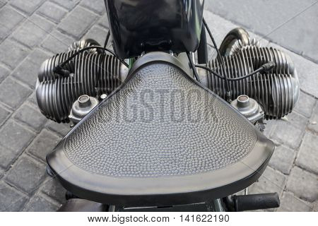 Old motorcycle vintage leather saddle over pavement background