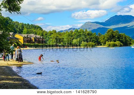 People having fun on a sunny summer day at the Loch Lomond lake in Scotland, 21 July 2016