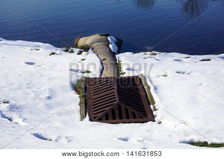 JOLIET, ILLINOIS / UNITED STATES - NOVEMBER 24, 2015: A culvert allows storm water to drain into a small lake in a residential area of Joliet.
