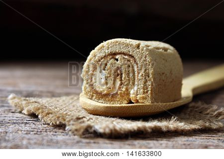 rool cake on wooden spoon coffee roll cake close up