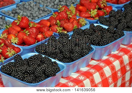 Baskets of strawberries blueberries and blackberries at market