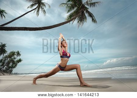 Beautiful sporty fit yogini woman practices yoga asana Virabhadrasana - warrior pose , on the beach
