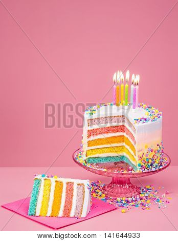 Colorful rainbow Birthday cake with candles over a pink background.