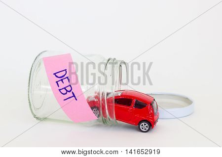 horizontal photo of red car toy going into the glass bottle with the word DEBT on its pink label.