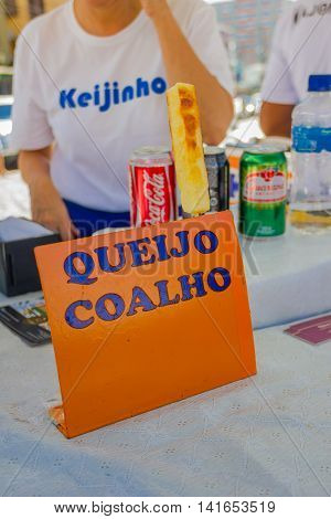 CURITIBA , BRAZIL - MAY 12, 2016: market stand sign offering grilled cheese, with one sample over the sign, cocacola and guarana cans behind the sign.