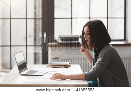 Lawyer or notary public on workplace working with documents. Successful female legal adviser reading files in office