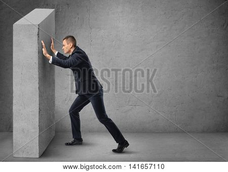 Businessman pushing a concrete wall. Hard work. Struggle and strain. Business staff. Office clothes.