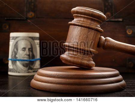 Judge gavel close up on brown wooden background In background mode a bundle of hundred-dollar bills