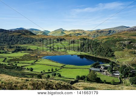 Gorgeous Watendlath valley from High Seat in the Lake District. The deep sapphire lake nestles in an emerald green vale surrounded by Lakeland Fells on a glorious sunny day under a blue sky