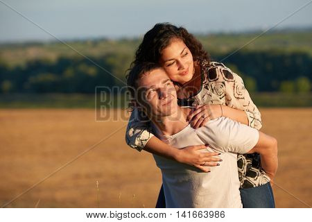 romantic young couple having fun on wheaten field background at evening, summer season, girl riding on man back