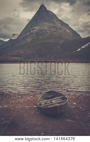 Lonely boat on the shore of wild mountain lake, Innerdalen, Norway